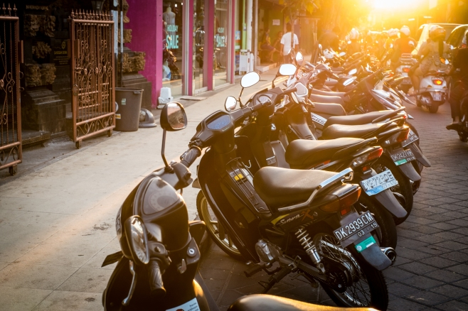 Basking in the afternoon sun, motorbikes lined up alongside Legian street for tourists to rent.